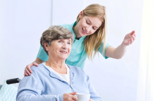old woman sitting on the wheelchair and her female caregiver assisting to her