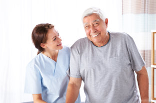 female caregiver assisting to her old man patient to walk