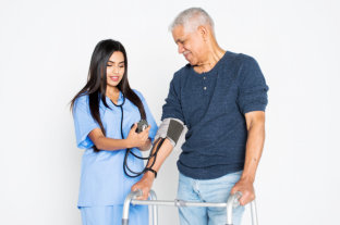 female caregiver doing blood pressure to her old man patient