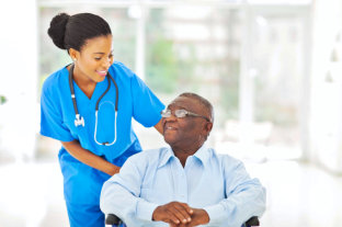 female caregiver with stethoscope looking to her old man patient sitting on the wheelchair