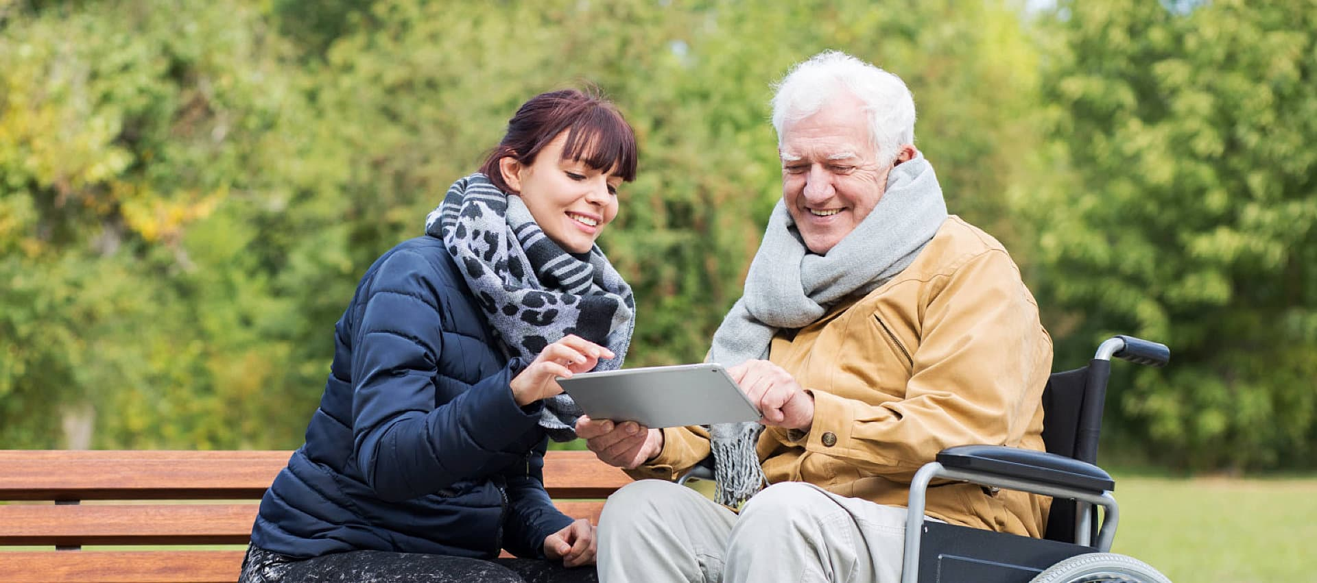 young female teaching the old man to used tablet