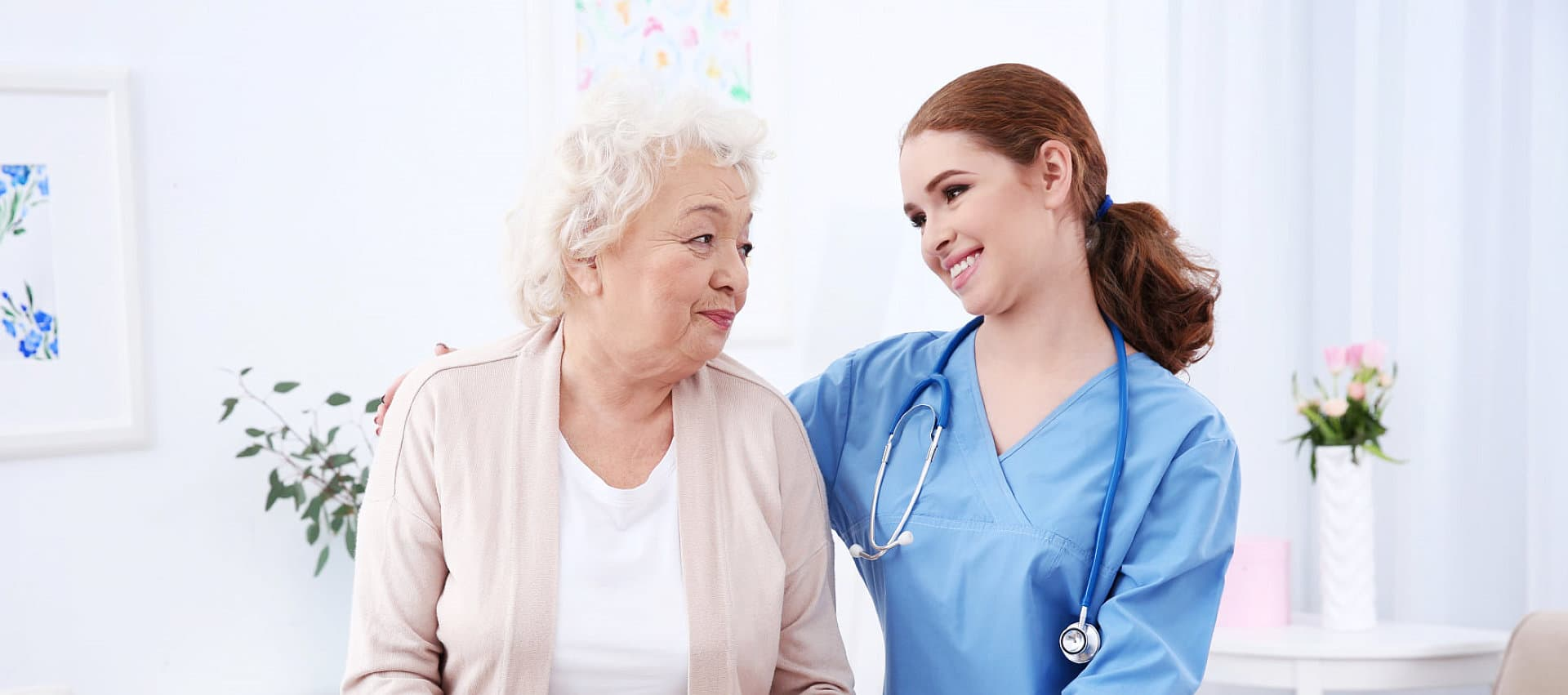 female caregiver with stethoscope with her old woman patient looking to each other