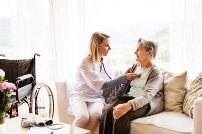 female caregiver checking the heart beat to her old woman patient