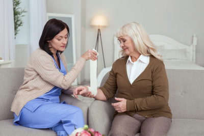 female caregiver aiding to her old woman patient