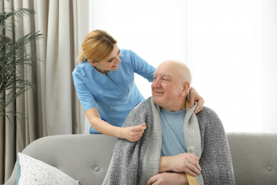 female caregiver and her old man patient sitting on the couch