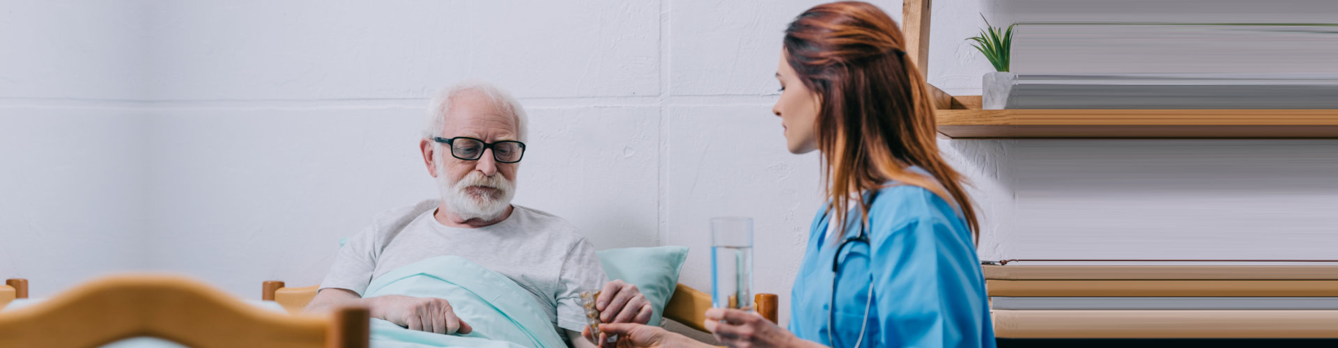 female caregiver assisting to her old man patient to drink his medicine while lying on the bed
